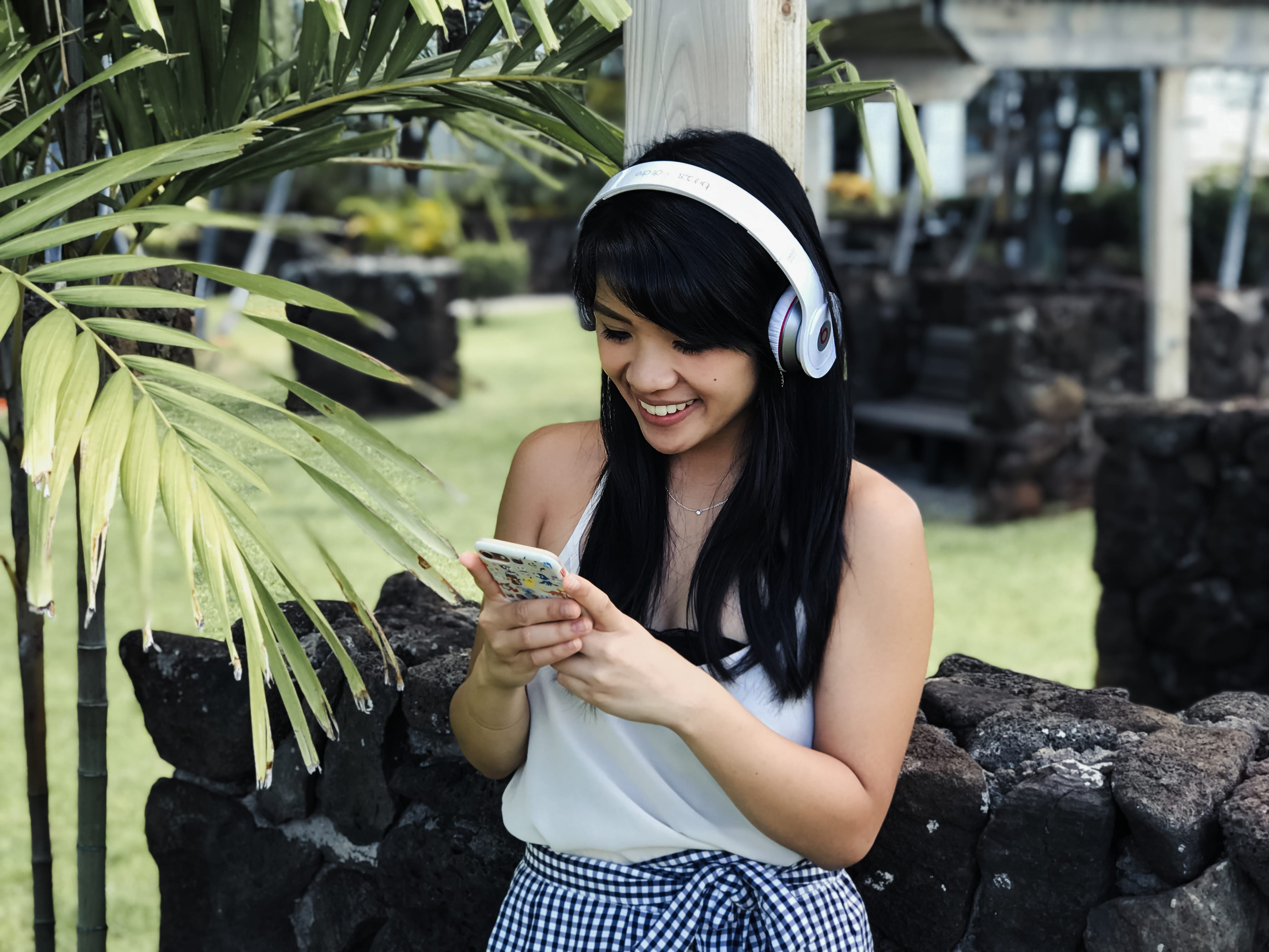 A girl looking at her device listening to a podcast